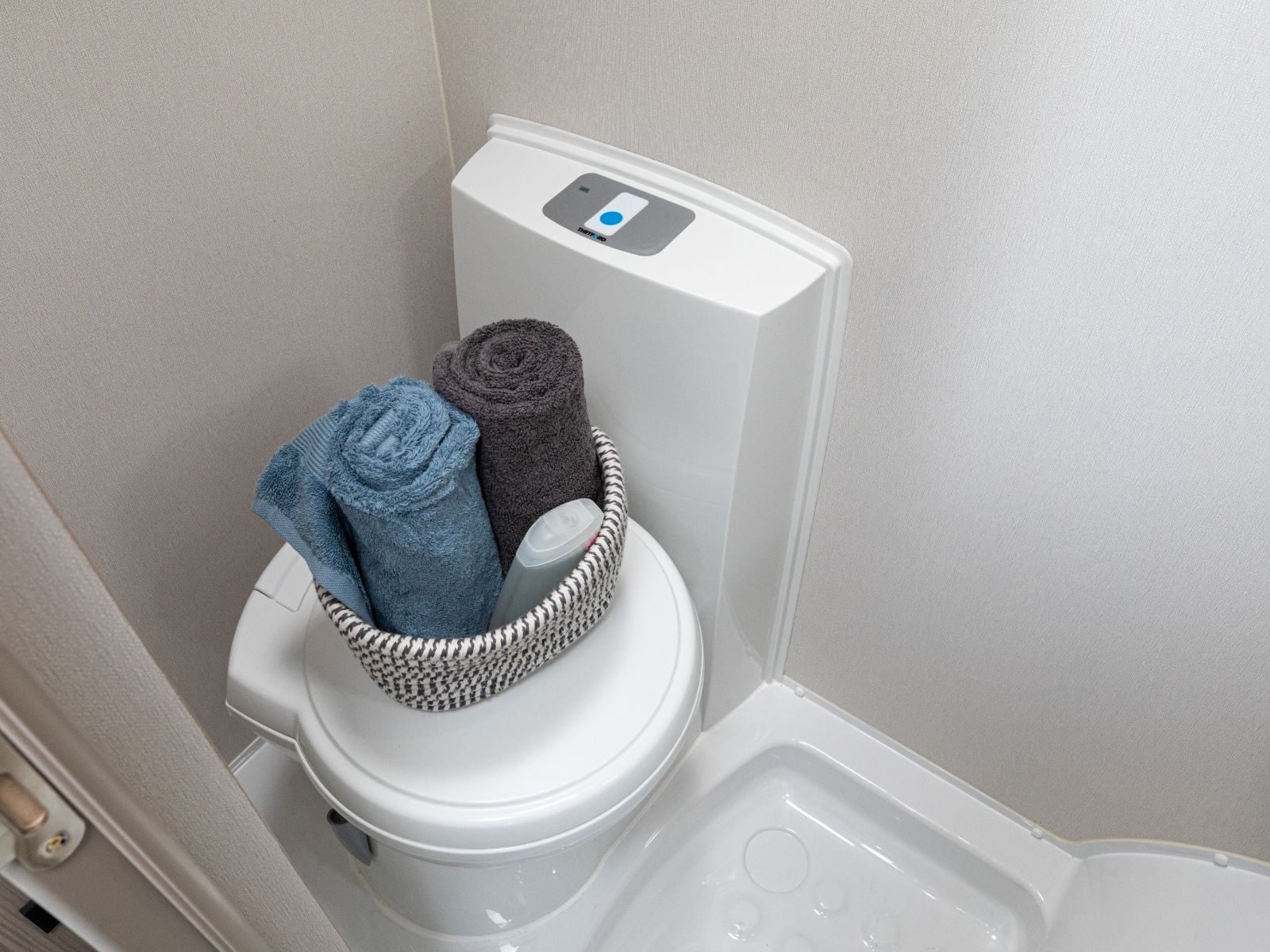 Toilet with basket of towels sat on top '