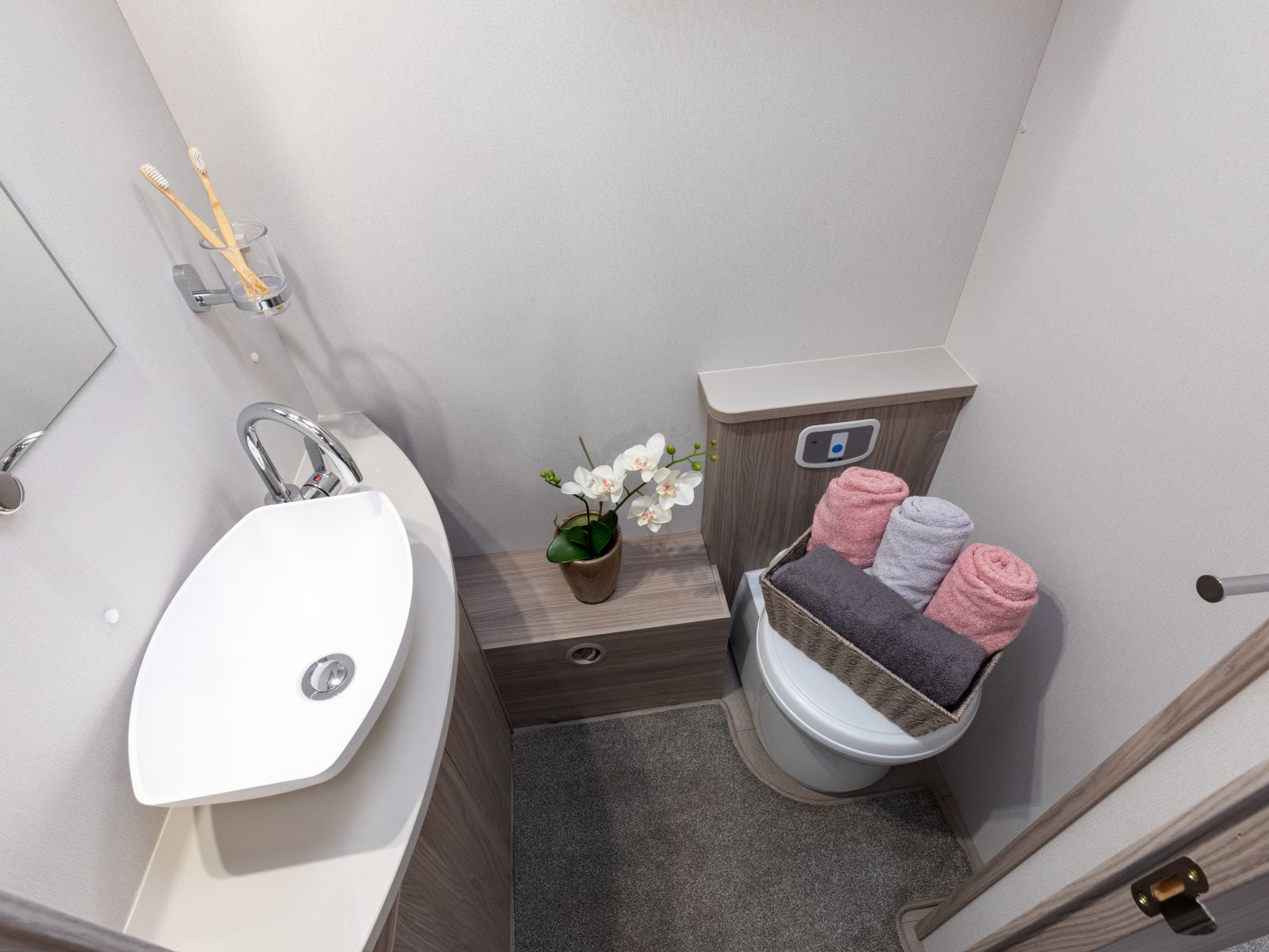 Toilet with basket of toiletries and towels on top '