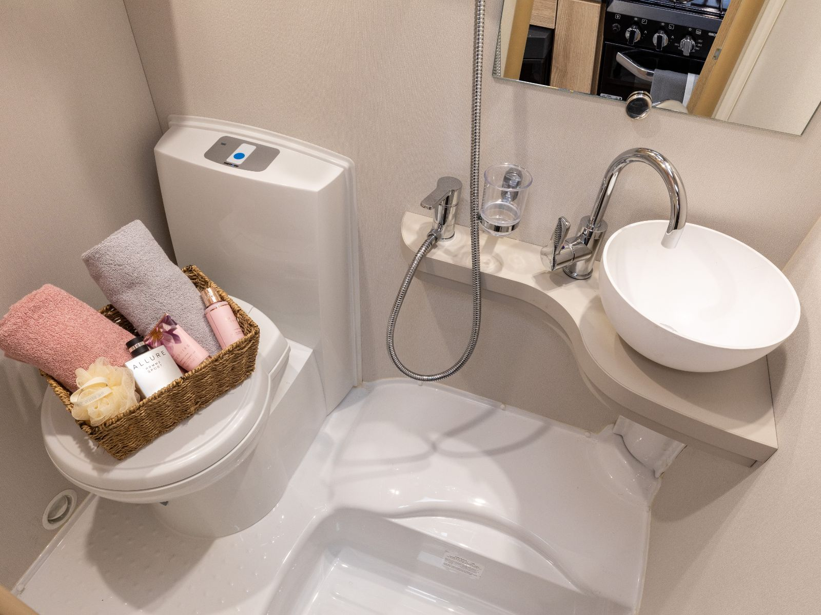 Bathroom layout with sink, shower controls and toilet with assortment of toiletries'