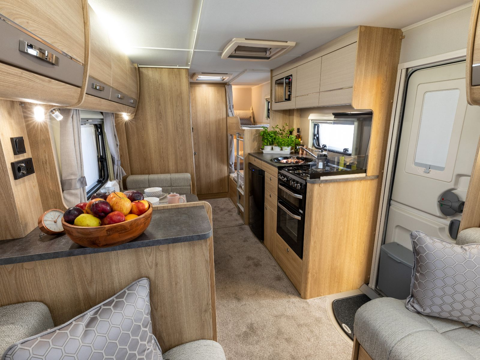 Lounge area with a view of the dining table, kitchen and double bunk beds at the rear of the caravan