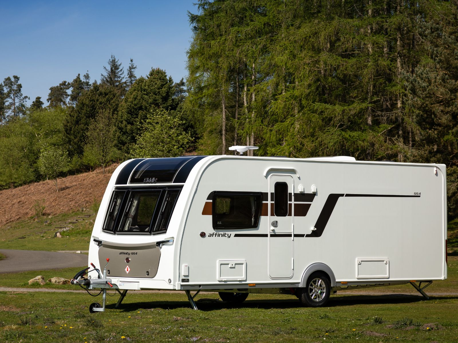 Affinity 554 Caravan parked in campsite with forest in background